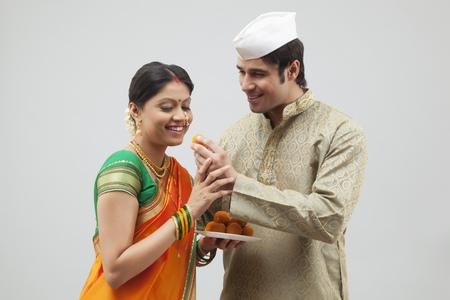 kurta: Maharashtrian woman about to eat laddoo from mans hand