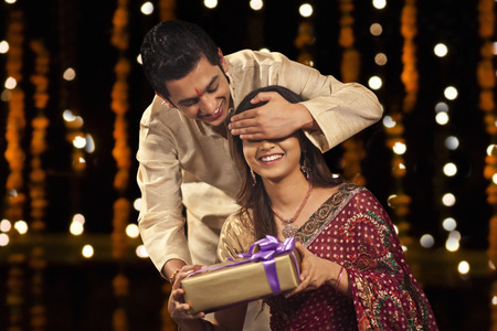 kurta: Brother surprising his sister with a gift Stock Photo