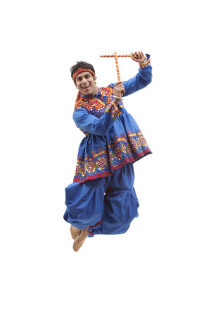 Portrait of happy young man in traditional wear jumping in mid air as he performs Dandiya Raas over white background Stock Photo