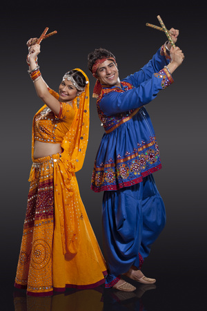 an entertainer: Full length portrait of happy young Indian couple performing Dandiya Raas over black background