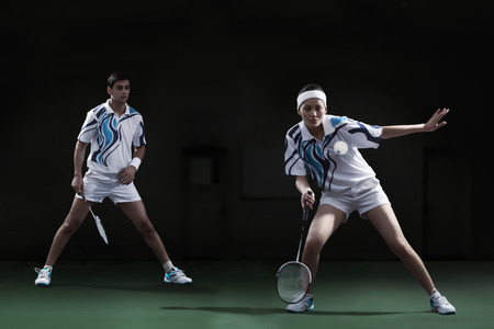 Woman hitting shuttlecock with badminton racket with partner looking at her Stok Fotoğraf