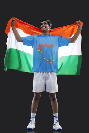 Full length of young man in sportswear holding Indian flag isolated over black background