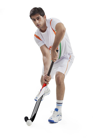 Portrait of young man playing field hockey isolated over white background Stock Photo