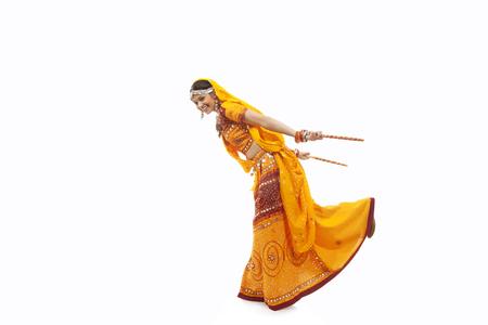 Full length portrait of young woman in chaniya choli performing Dandiya Raas over white background Stock Photo