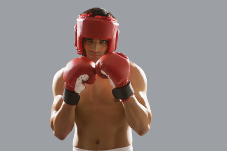 build up: Portrait of young male boxer wearing gloves and head protector isolated over gray background