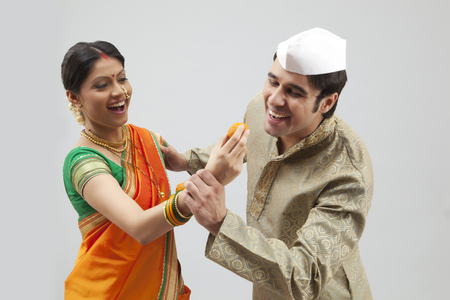 gajra: Maharashtrian man trying to eat a laddoo from a womans hand Stock Photo