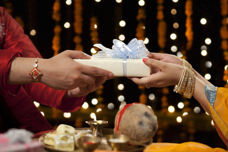 Close-up of a man giving gift to his sister Stock Photo