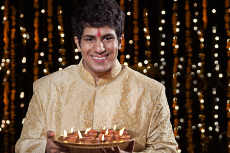 Portrait of a man holding a tray of diyas Stock Photo
