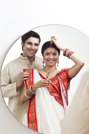 identidad cultural: Bengali woman putting sindoor on her forehead while husband watches on