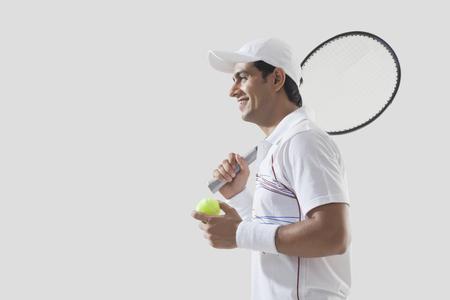 Side view of young man holding tennis racket and ball isolated over gray background Stock Photo