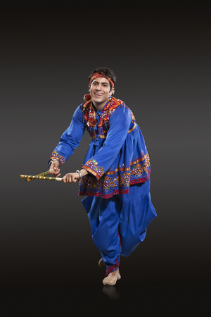 dhoti: Full length portrait of Indian man in traditional wear performing Dandiya Raas isolated over black background