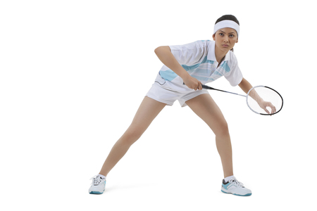 Young woman in sports wear playing badminton against white background