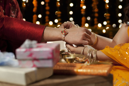 Close-up of a woman tying rakhi on her brothers hand