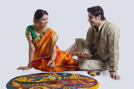 nose ring: Maharashtrian couple placing diyas on rangoli