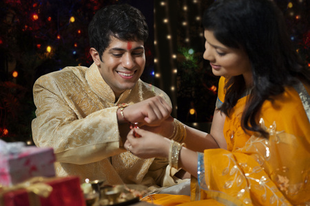 down lights: Woman tying rakhi on her brothers hand Stock Photo