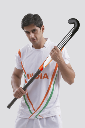 Portrait of confident young man holding hockey stick isolated over gray background