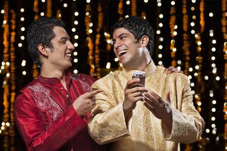 kurta: Men laughing at sms on mobile phone Stock Photo
