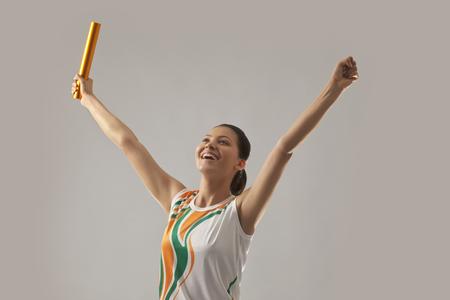Vrouwelijke estafetteloper het vieren overwinning die over grijze achtergrond wordt geïsoleerd Stockfoto