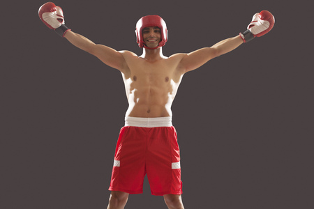 Portrait of an Indian male boxer with arms outstretched celebrating victory isolated over black background