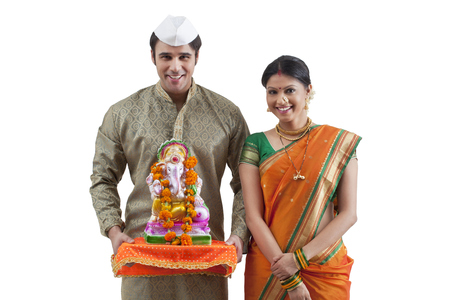 Portrait of a Maharashtrian couple with a Ganesh idol Stock Photo