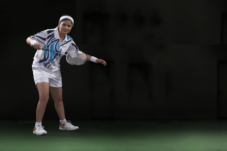 Full length portrait of young woman playing badminton isolated over black background