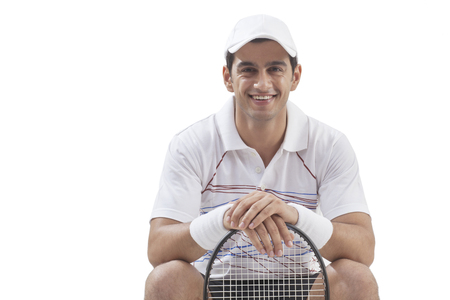 Portrait of young man with tennis racket isolated over white background