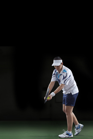 Female tennis player preparing to serve over black background Stock Photo