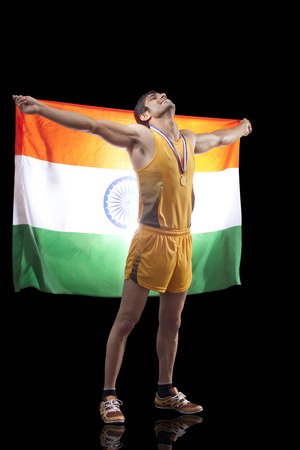he: Full length of male medalist holding Indian flag as he looks up over black background