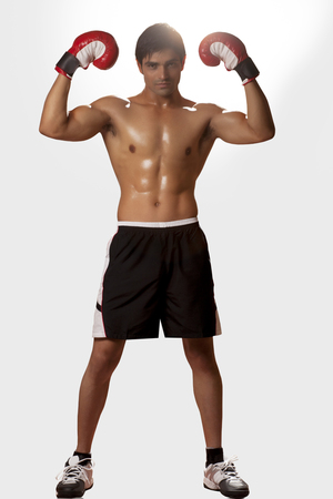 Full length portrait of young male boxer flexing muscles over white background
