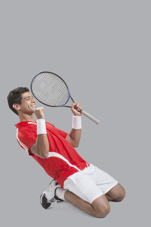 side shot: Happy male tennis player celebrating success over gray background