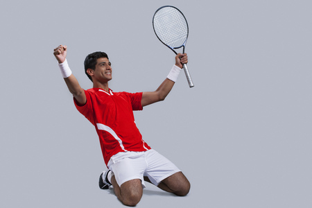Happy male tennis player celebrating victory isolated over gray background Stock Photo