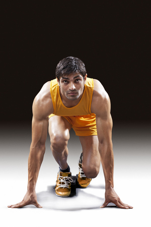 Male runner ready to sprint out of starting blocks against black background