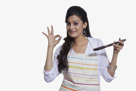 Portrait of a woman with a cooking utensil giving ok sign Stock Photo