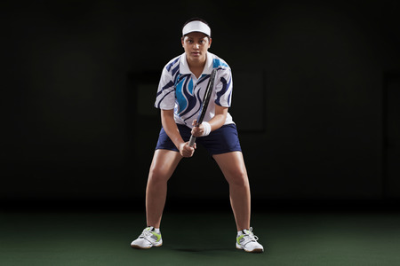 Portrait of young female player holding tennis racket over black background Stock Photo