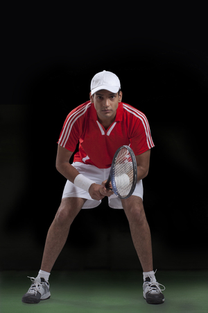 Full length of young Indian man playing tennis over black background