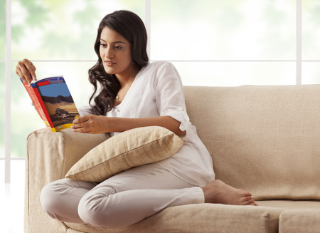 Woman reading a book on a sofa Stock Photo