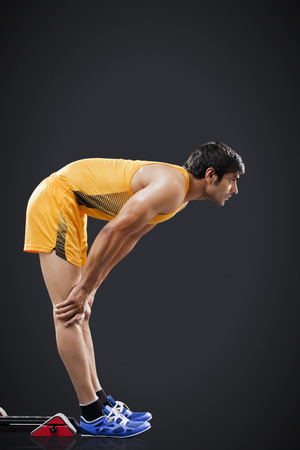Profile shot of young male runner at starting line against black background Stock Photo