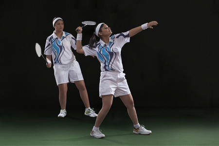 Young female players playing doubles badminton against black background
