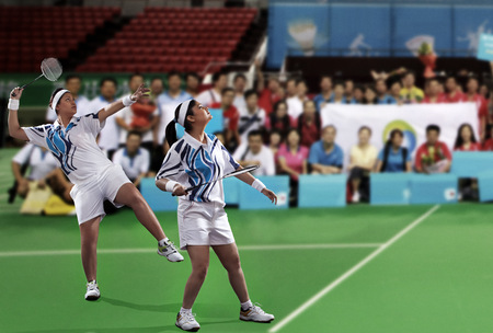 Young female players playing doubles with spectators in the background Stock Photo