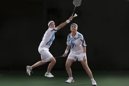 Young female players in sportswear playing doubles badminton against black background