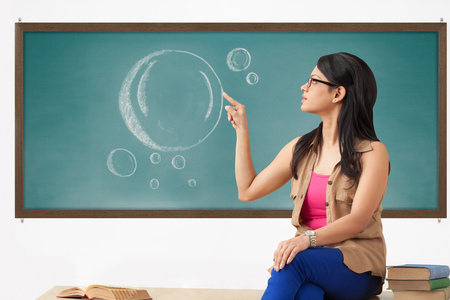 Female college student pointing at blackboard