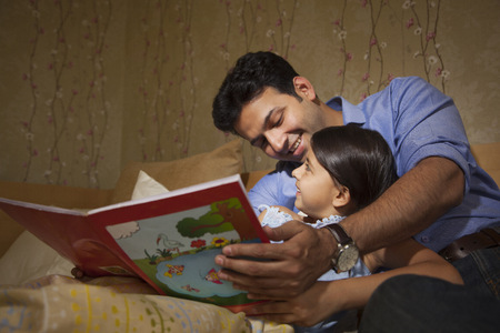 single story: Father reading a story to his daughter