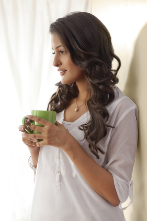 only 1 woman: Woman with a mug of tea thinking Stock Photo