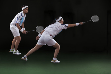Profile shot of young women playing doubles badminton over black background