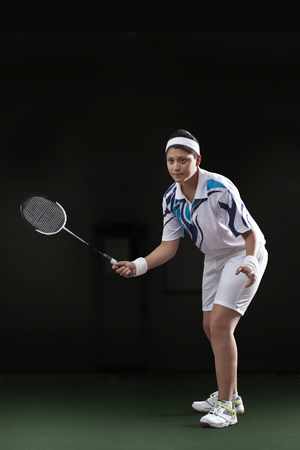 Young woman in sportswear playing badminton isolated over black background