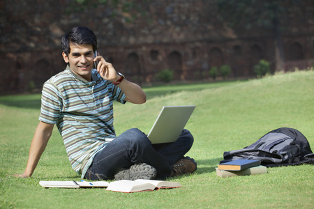 cross legged: Portrait of a student talking on a mobile phone Stock Photo