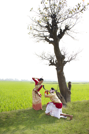Bihu man blowing on a pepa while Bihu woman dances to his tune Stock Photo