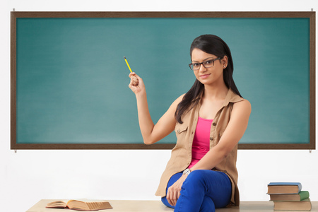 cross legged: Female college student gesturing to blackboard Stock Photo