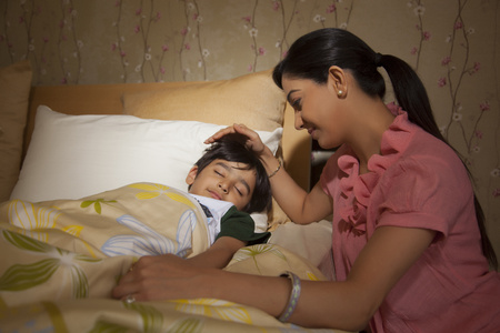 bangles hand: Mother putting her son to sleep