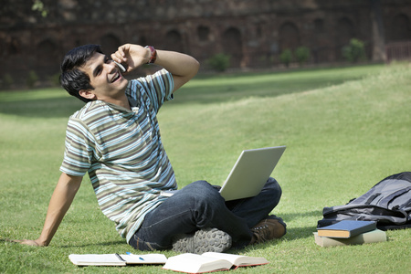 Student with a laptop talking on a mobile phone